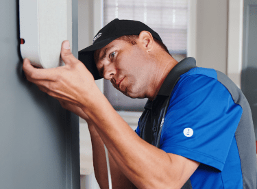 Man installing a home cell phone signal booster